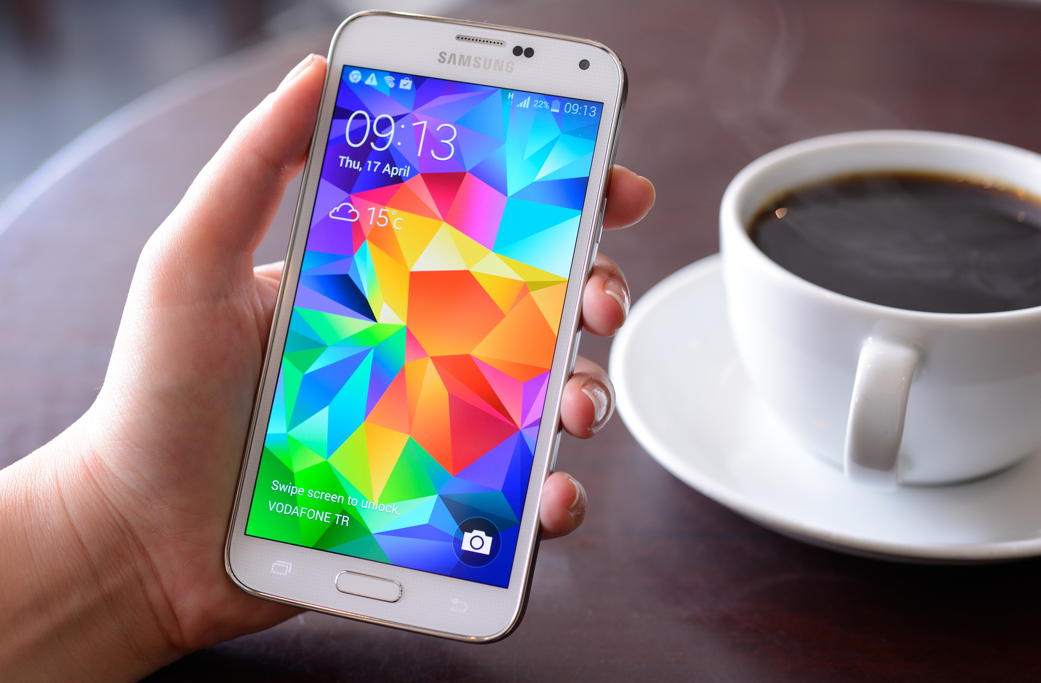 Person using a Samsung Galaxy with coffee in background