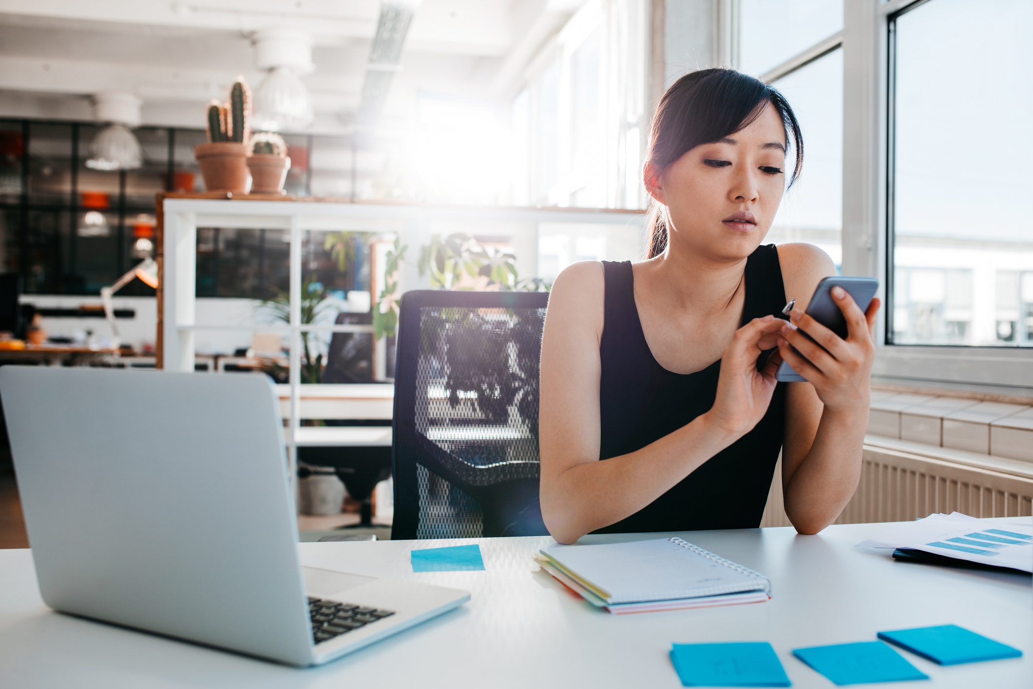 Woman using smartphone at desk with notepad
